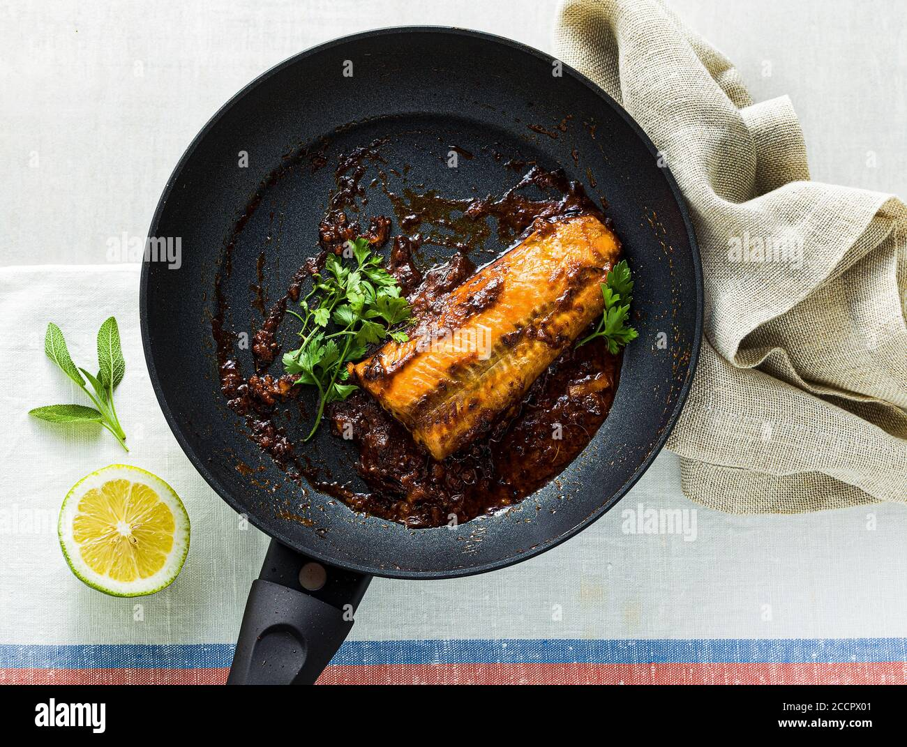 fillet of pink salmon in tomato-coconut sauce in a non-stick frying pan with parsley on a table with a linen tablecloth. healthy family food Stock Photo