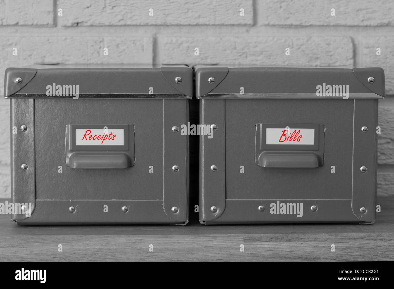 Storage boxes with receipts and bills written on labels in red.  With a grey brick background Stock Photo
