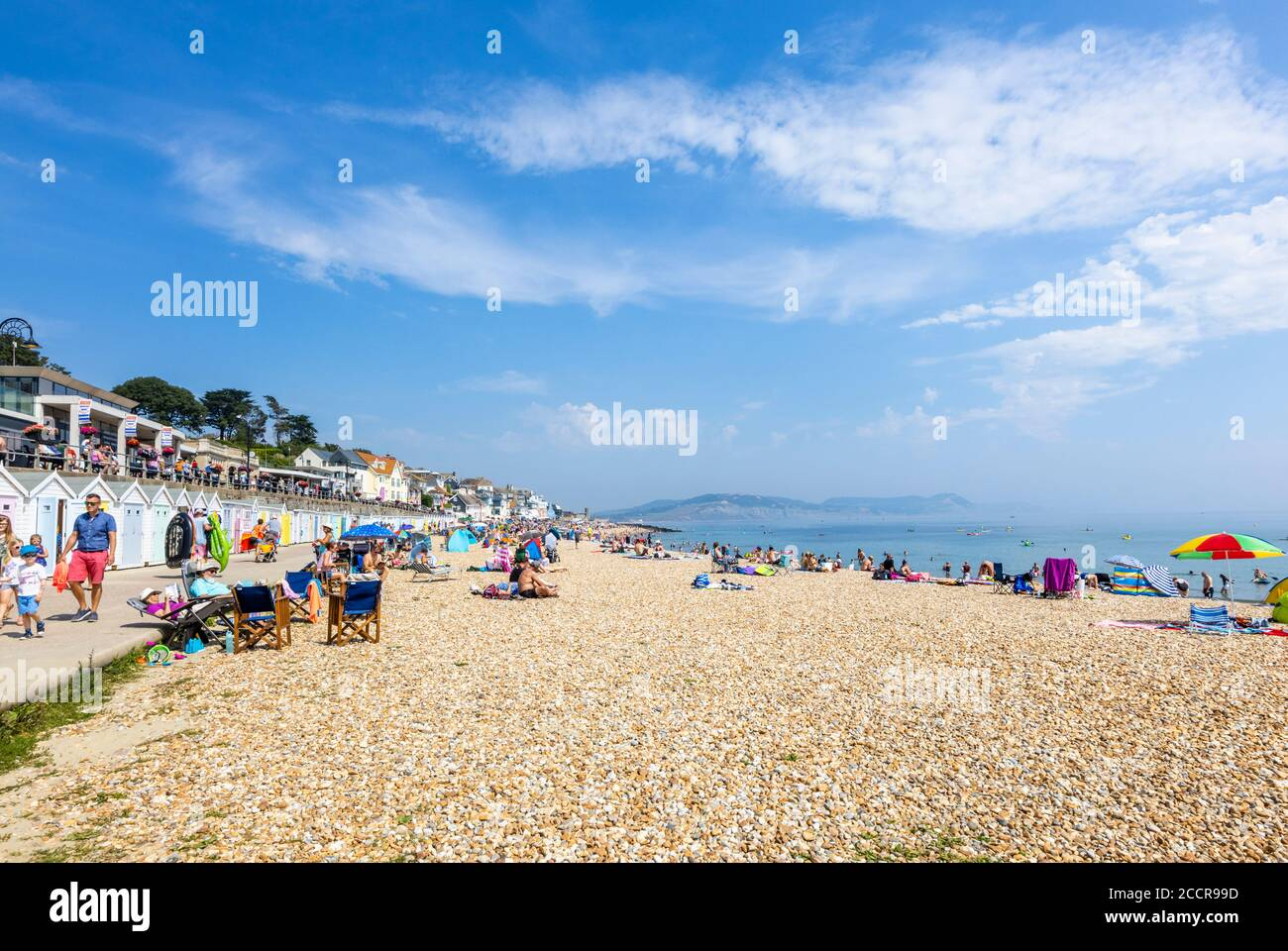 The stony beach and seafront in high season at Lyme Regis, a popular seaside holiday resort on the Jurassic Coast in Dorset, south-west England Stock Photo
