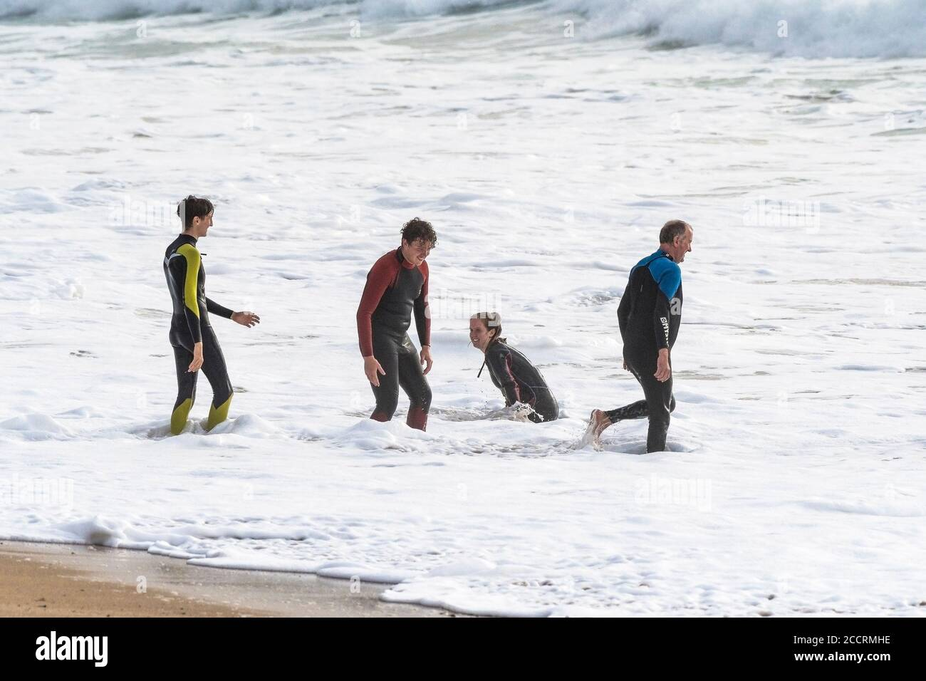 Holidaymakers in wetsuits enjoying themselves in the surf on Fistral Beach in Newquay in Cornwall. Stock Photo