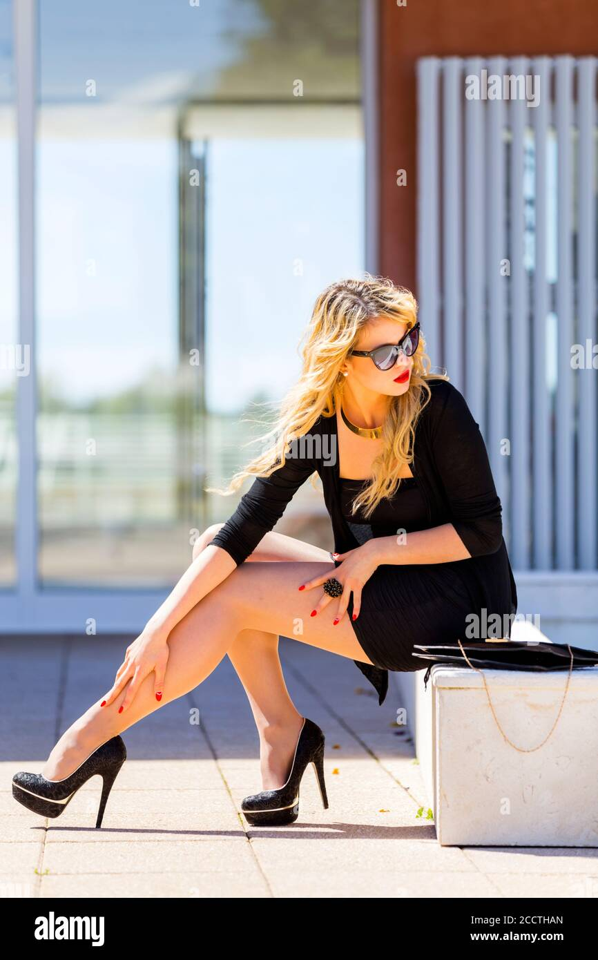 Fanciful young woman in Black clothing minidress and high-heels under sunshine on street in town city looking back over shoulder expecting somebody Stock Photo