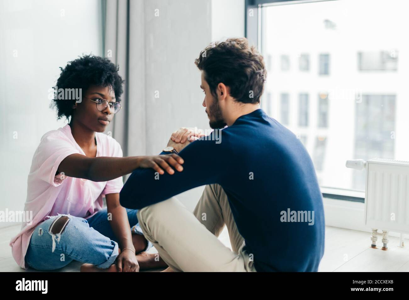 Young African woman and Caucasian man sitting near the window, staring at each other meditating together, free their minds from thoughts and worries. Stock Photo