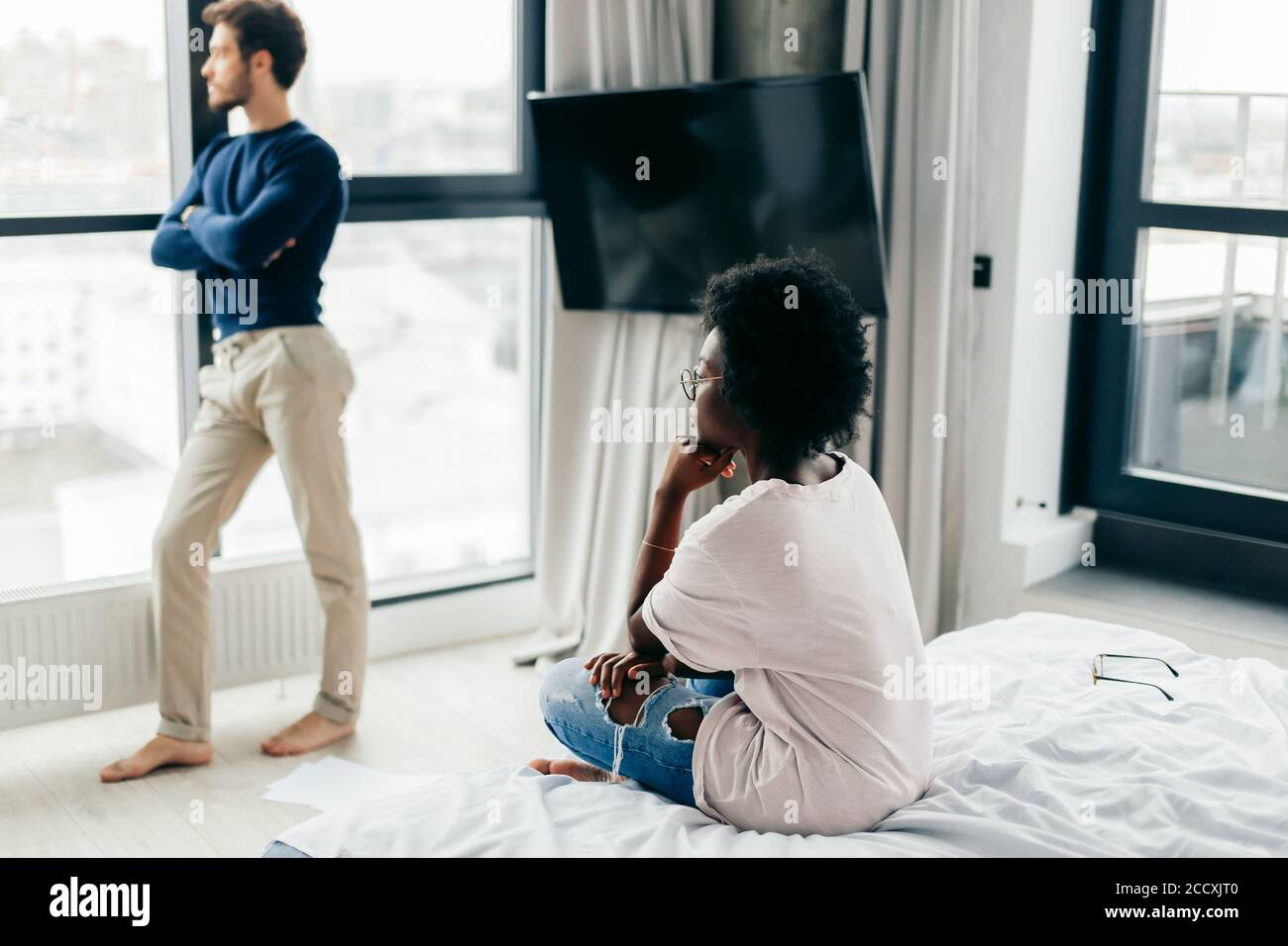 Frustrated african woman feeling offended and depressed after she knew that the engagement has failed. Her would-be groom of european appearance just Stock Photo