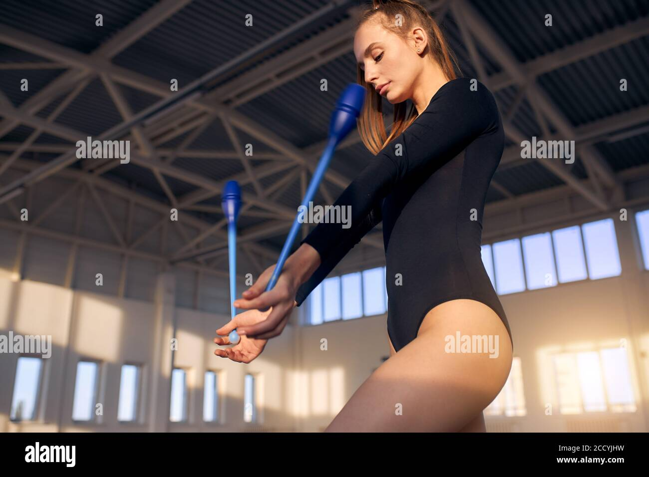 Charming beautiful girl training in storts hall, keeping dark blue gymnastics clubs in hands,looks down, shot from below, active lifestyle concept Stock Photo