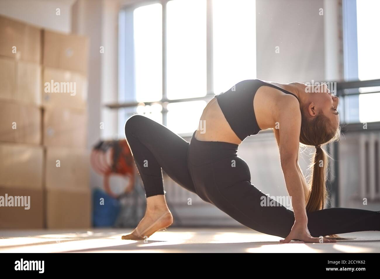 portrait of young charming gymnast bending crab, stretching body back intensively, looks up, health life style concept Stock Photo