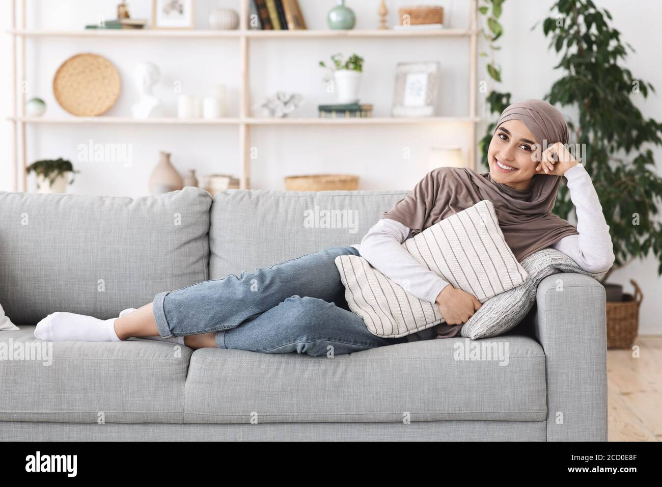 Relaxed Arabic Woman Lying On Couch At Home Cuddling Pillow Enjoying Weekend Stock Photo Alamy