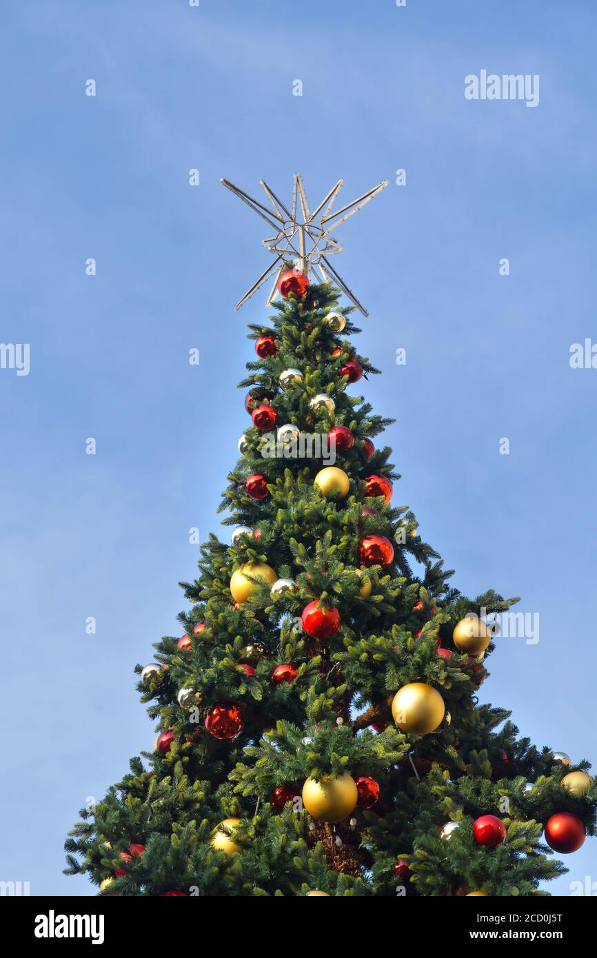 Decorated Christmas Tree With Red Gold And Silver Christmas Balls And A Silver Star On Top Against A Blue Sky Stock Photo Alamy