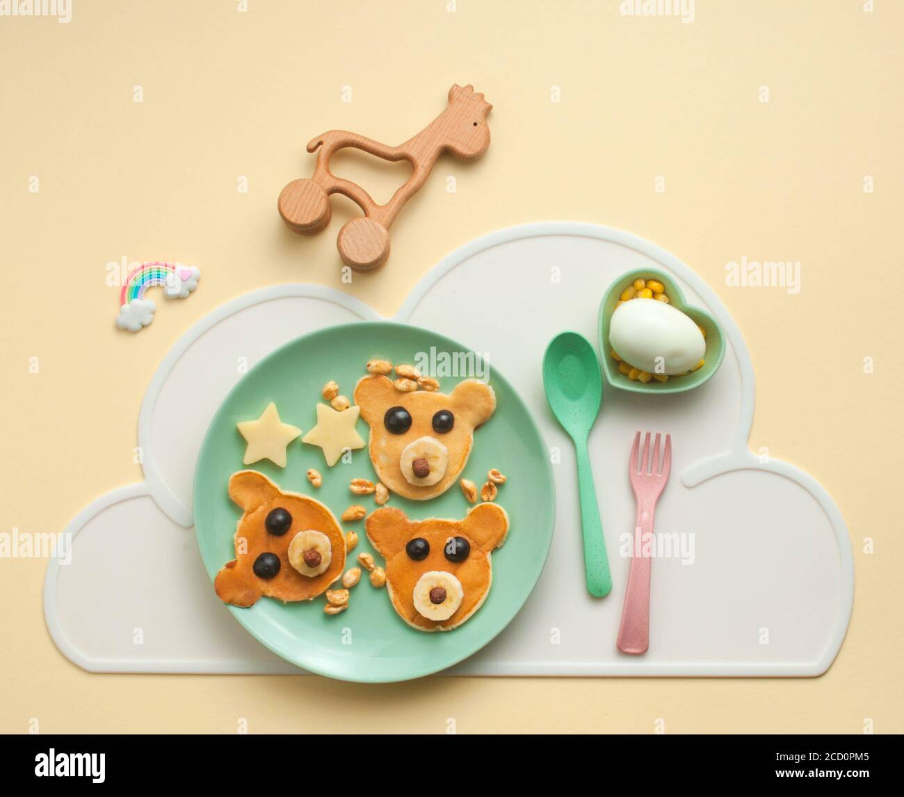 Top view of kid's breakfast. Green plate with funny pancakes on yellow background. Flat lay. Stock Photo