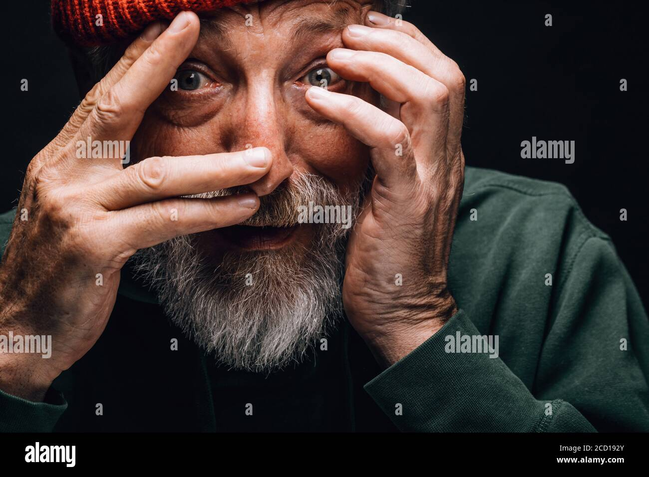 An elderly bearded man looking extremely surprised or frightened, protecting his face with hands, close up face portrait over black studio background. Stock Photo