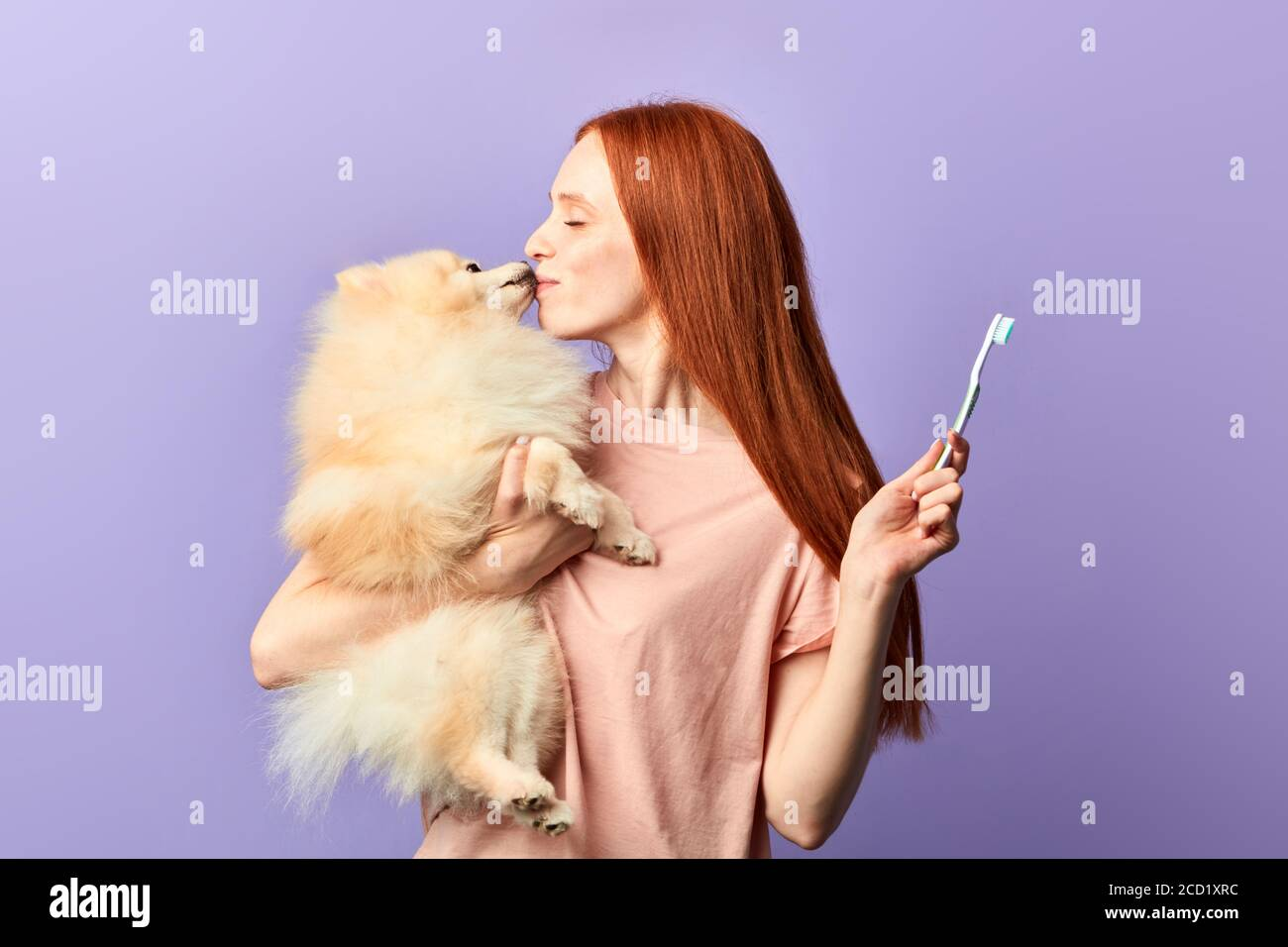 funny pleasant ginger girl kissing with her adorable dog. close up side view photo. isolated blue background, studio shot, lifestyle, free time, spare Stock Photo