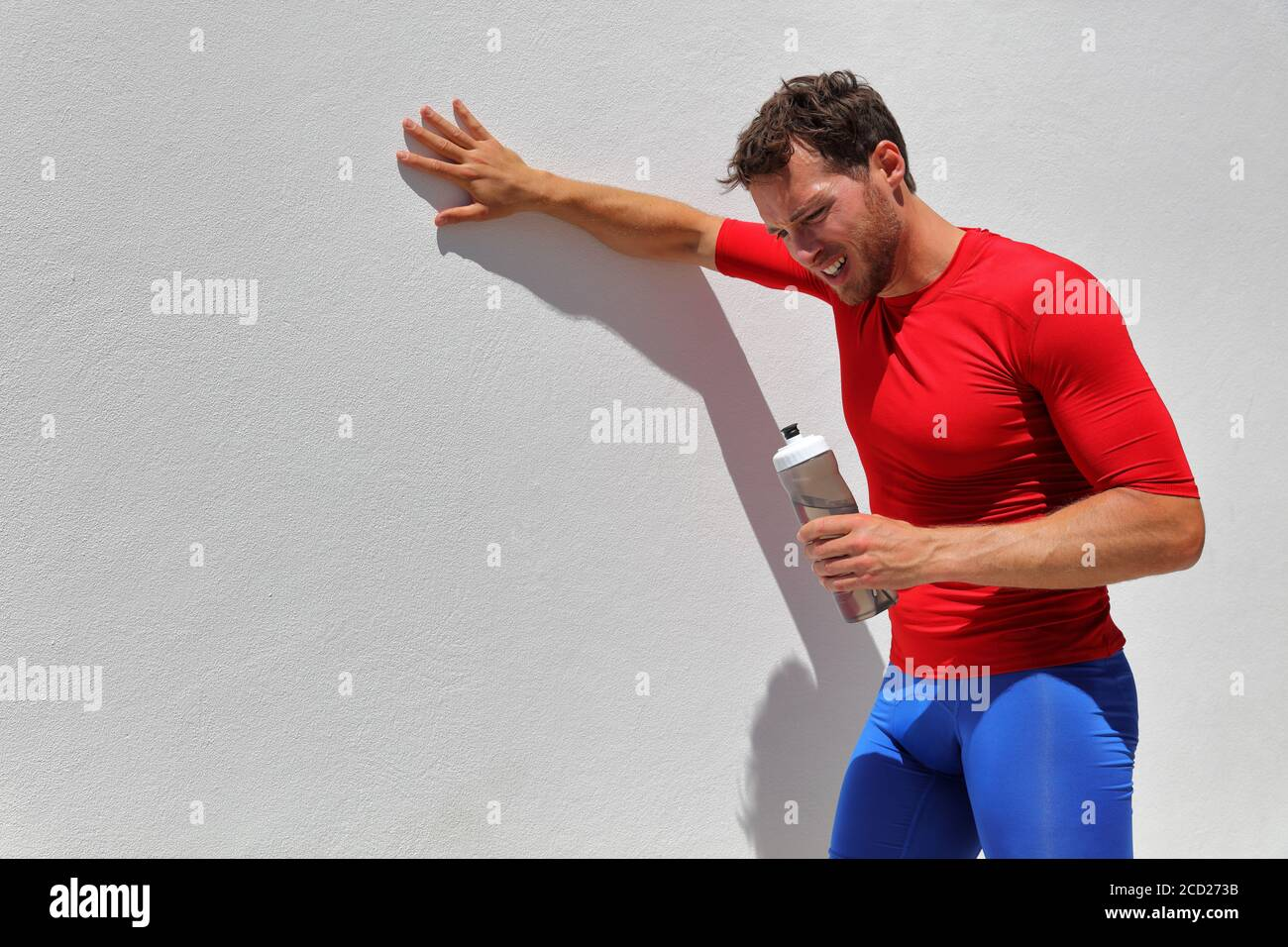 Tired exhausted dehydrated man runner drinking water bottle after workout. Running person taking a break after run. Fitness athlete breathing from sun Stock Photo