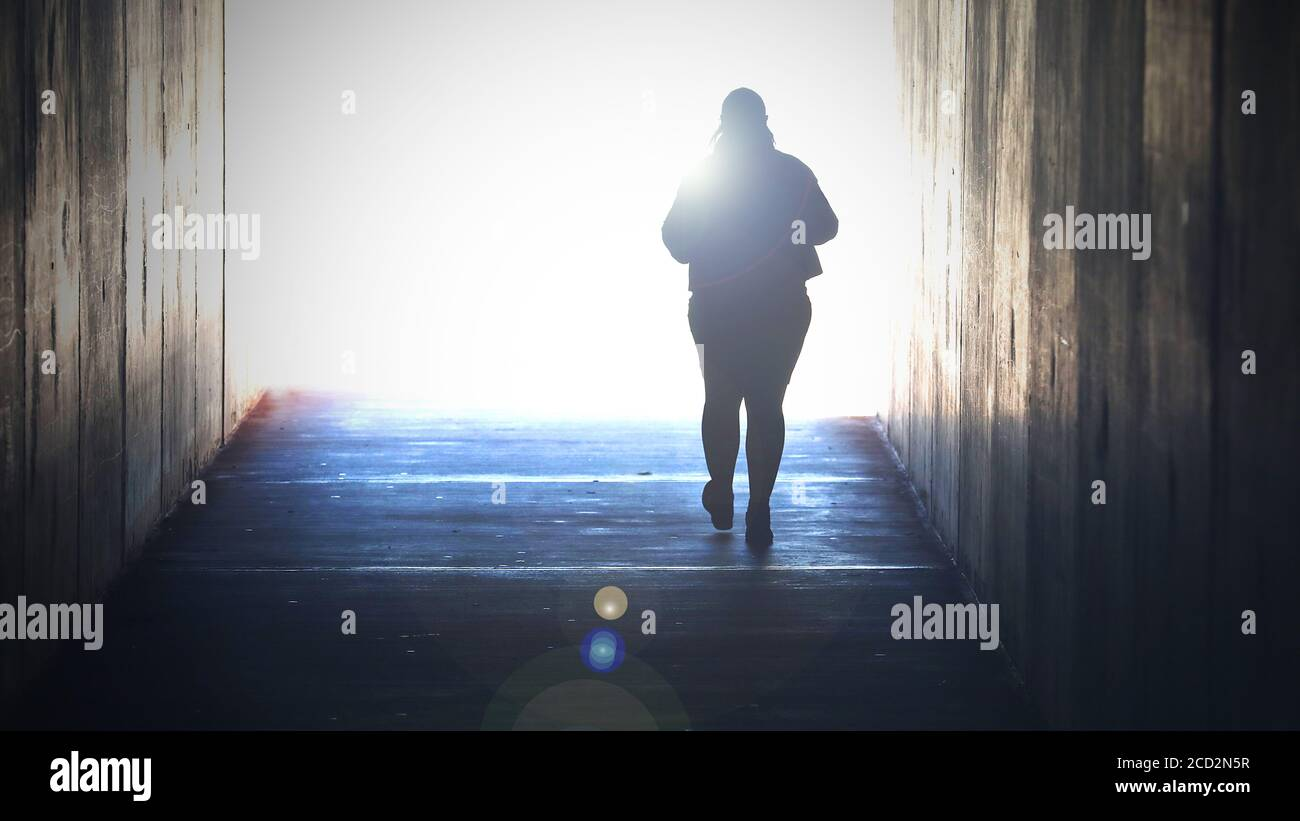 A lone isolated figure fading away heading or walking towards a bright light at the end of tunnel. Grief, death, dying suicide, faith concept. Crossin Stock Photo