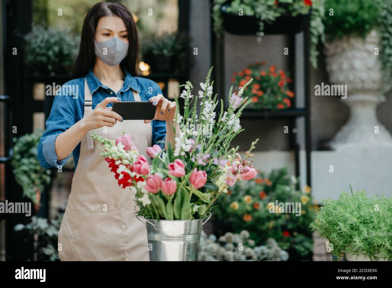 Florist at work. Woman in apron and protective mask makes photo on smartphone of bouquet Stock Photo