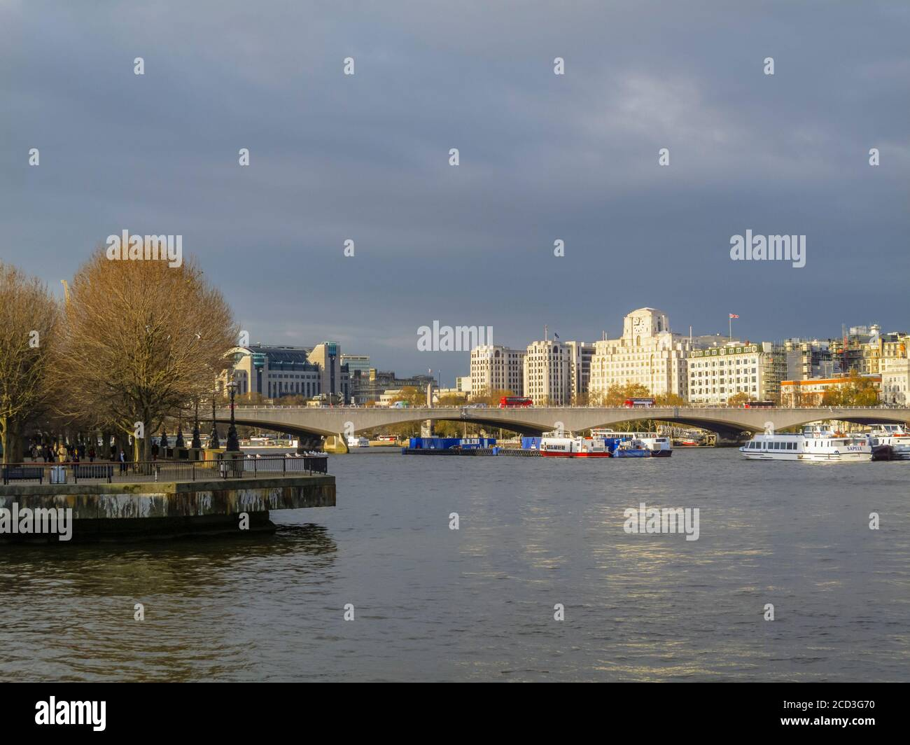 View along the River Thames over Waterloo Bridge to Shell Mex House, 80 Strand, and Charing Cross Station in winter under grey skies Stock Photo