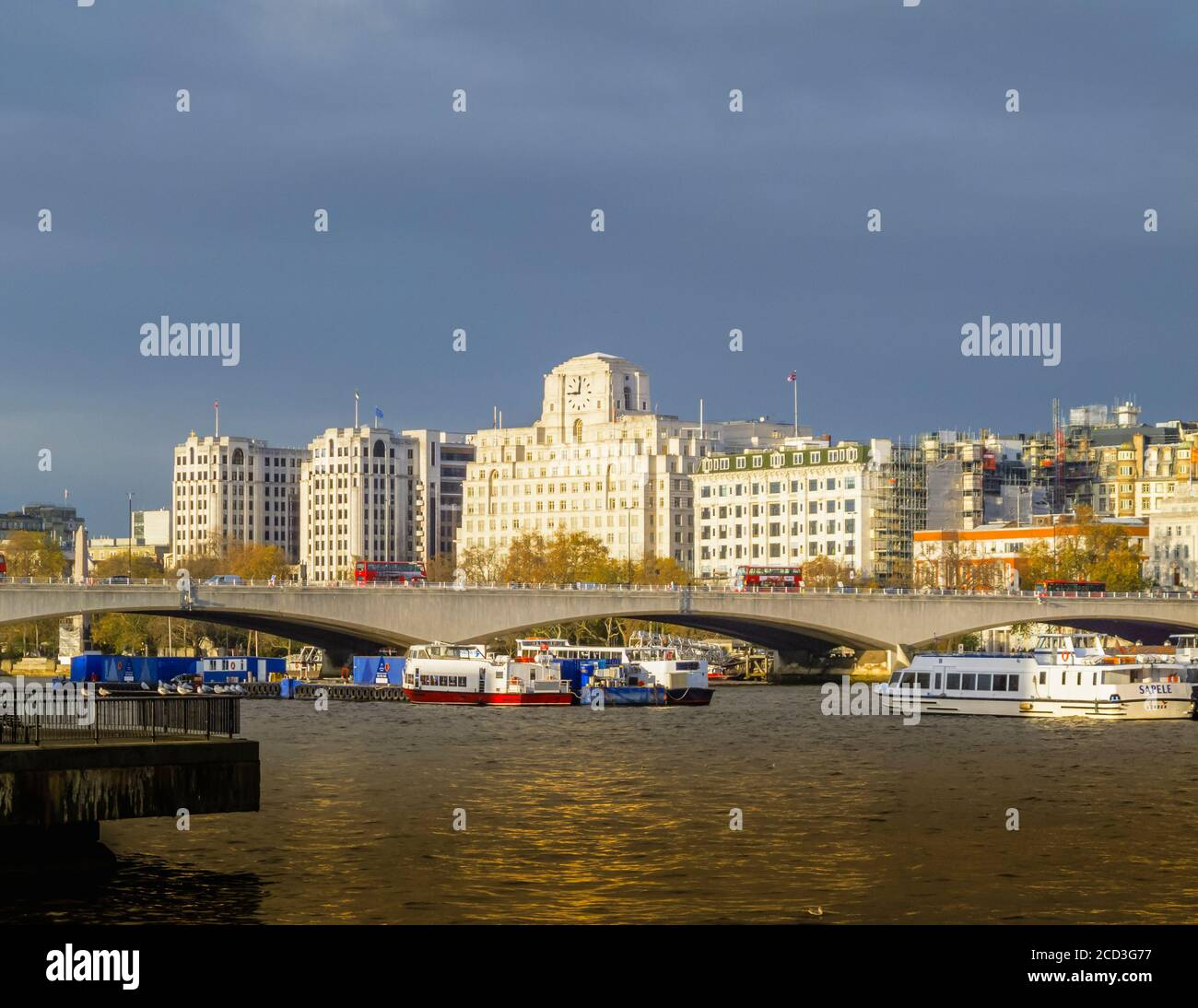 View across the River Thames over Waterloo Bridge to Shell Mex House in morning light in winter under grey skies Stock Photo