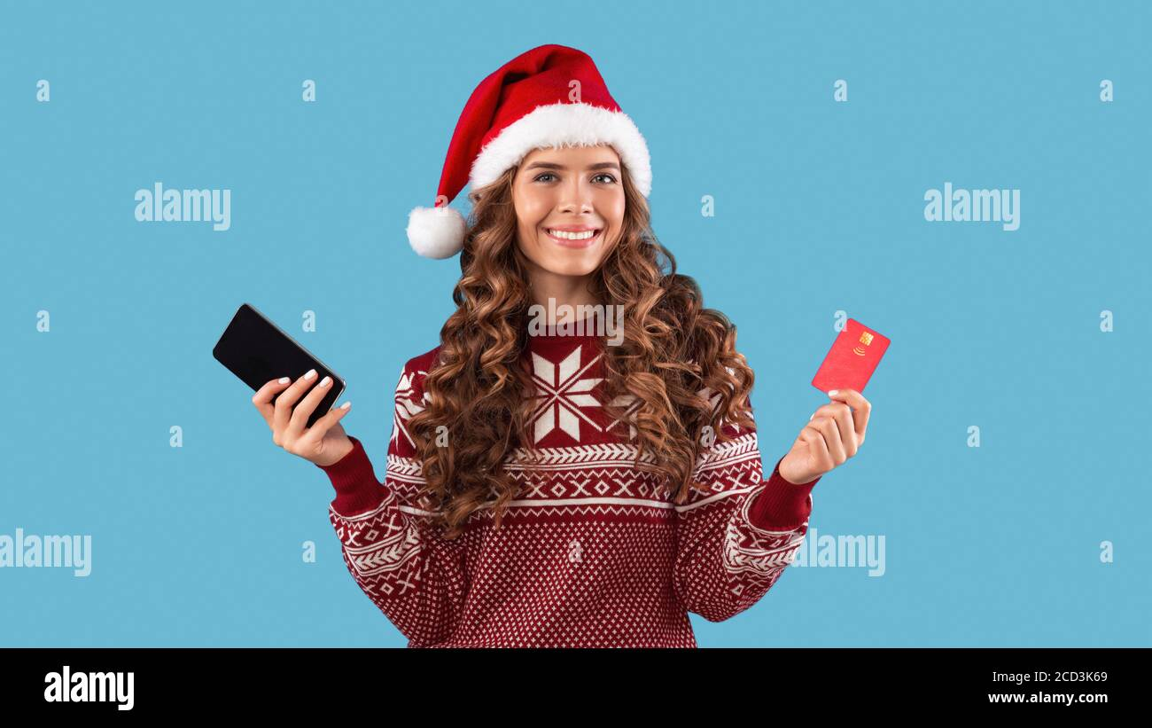 Online Christmas Shopping Lovely Girl In Santa Hat And Sweater Holding Mobile Phone And Credit Card On Blue Background Stock Photo Alamy