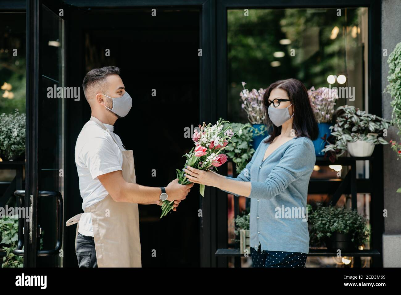 Customer service in flower shop. Man in protective mask gives bouquet to client Stock Photo