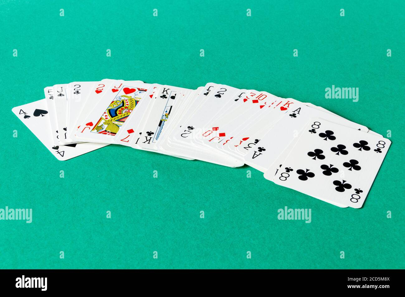 a pack of playing cards loosely fanned out on a card table 2CD5M8X
