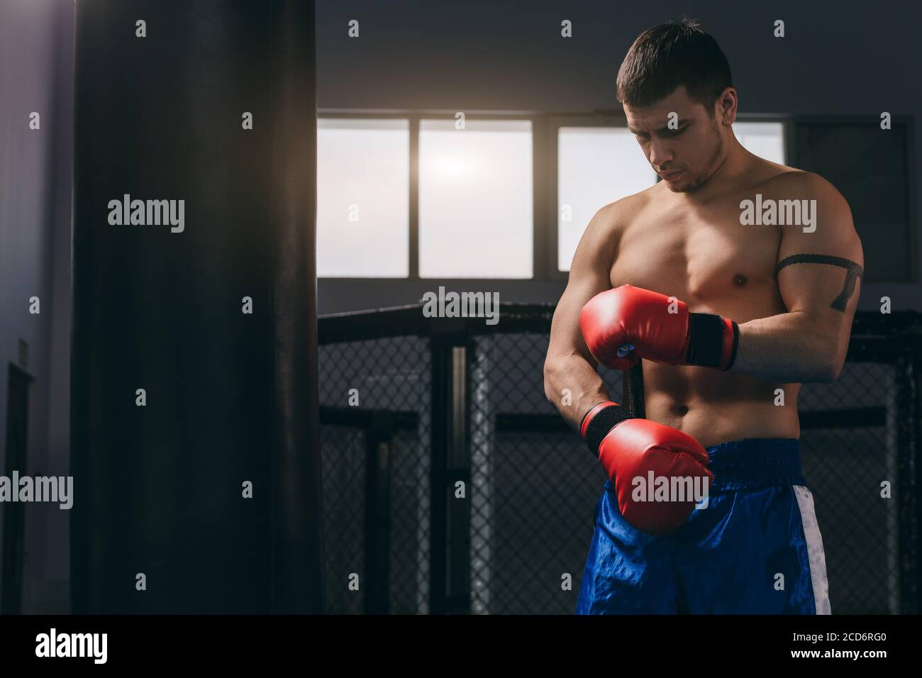 Young athletic man preparing for boxing competitions, training defense and attacks in fighting club, making punches in red boxing gloves and moving ar Stock Photo