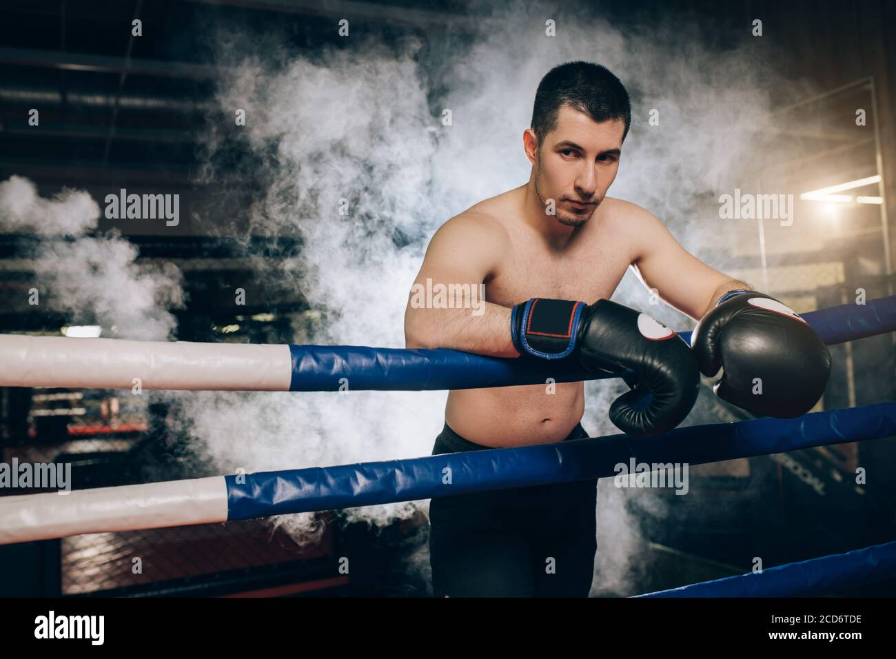 young caucasian boxer man stand wearing protective boxer gloves isolated over smoky ring. Man with sportive muscular body in full combat readiness to Stock Photo