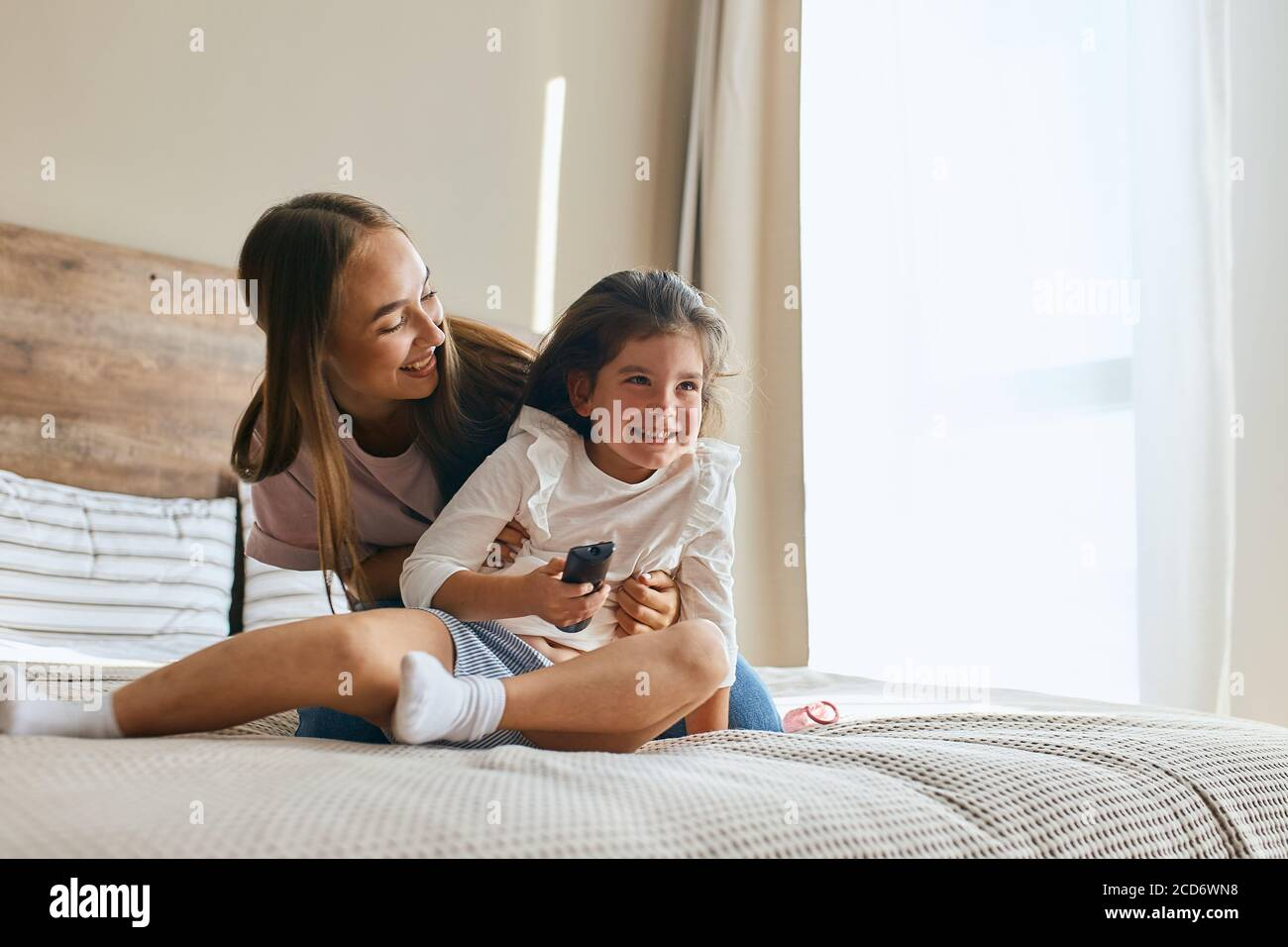 Young mother with her five years old little daughter dressed in casual outfit are relaxing and playing in the bed at the weekend together, lazy mornin Stock Photo