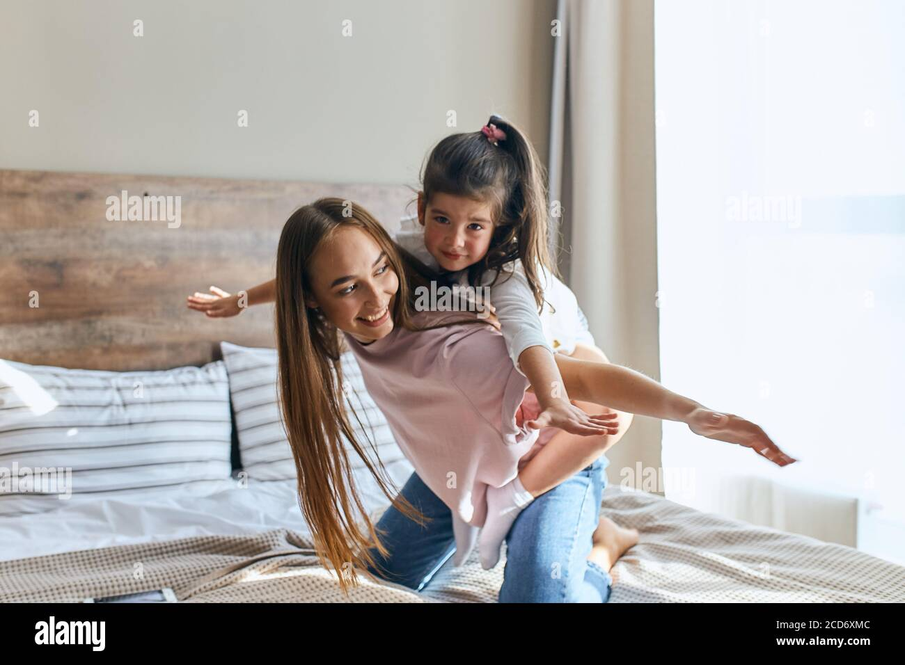 Attractive charming little girl on a piggy back ride with lovely young mom, looking at camera with calm face, woman with long hair playing with child Stock Photo
