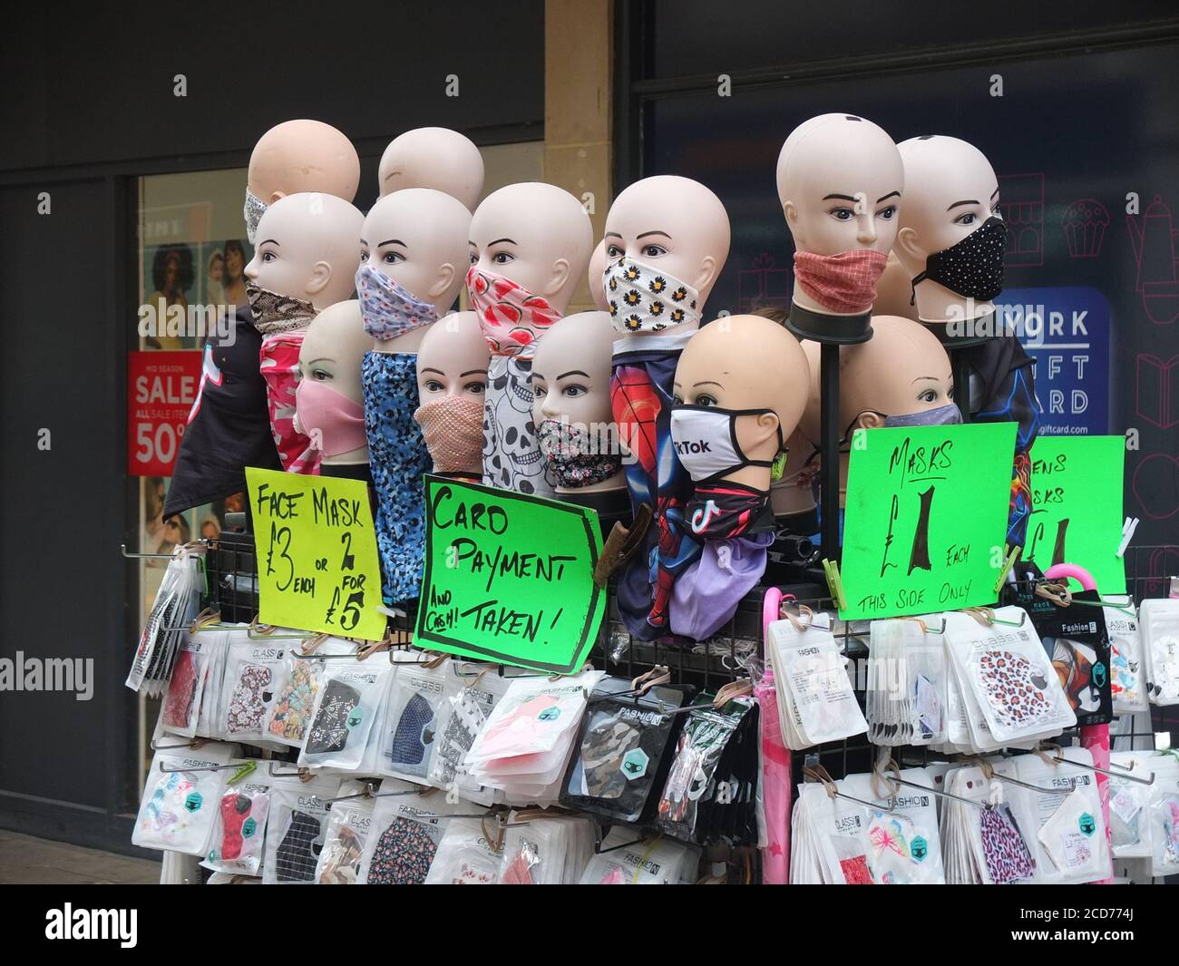 Street market stall with mannequin heads selling a variety of face coverings and masks to protect from spreading Coronavirus in York, UK Stock Photo