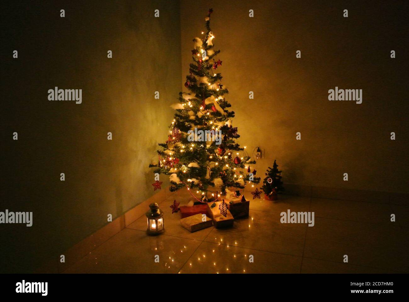 Lighted And Decorated Christmas Tree On A Dark Background With Presents And Lantern Underneath Warm String Lights Illuminates The Tree Stock Photo Alamy