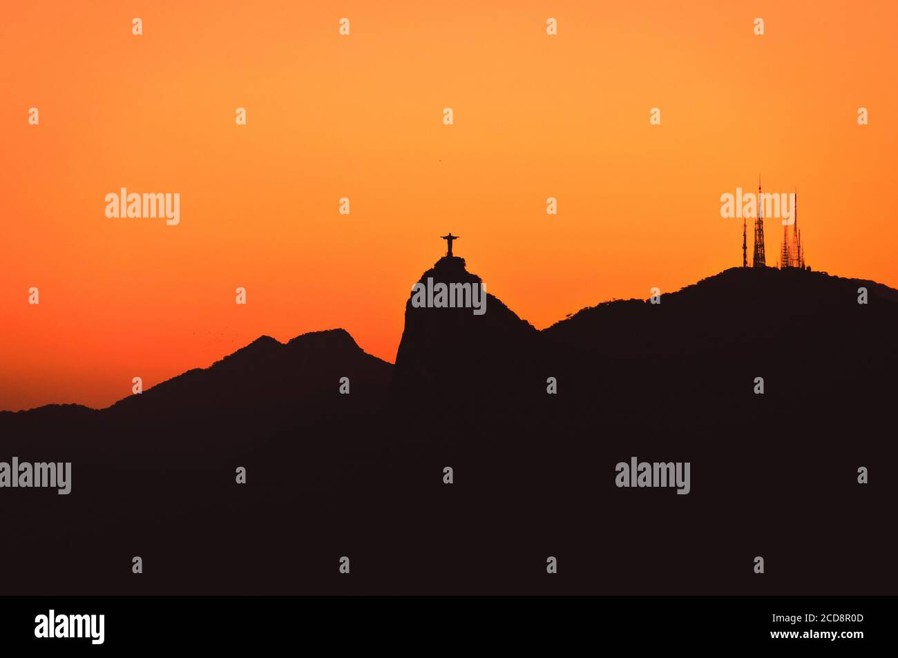 The famous Rio de Janeiro landmark - Christ the Redeemer statue and Corcovado mountain silhouette by sunset Stock Photo