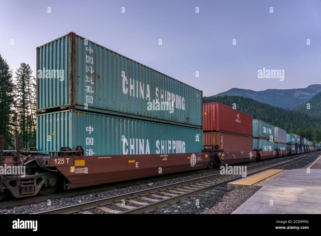 Shipping containers marked China Shipping travelling through America by rail in Montana. Stock Photo