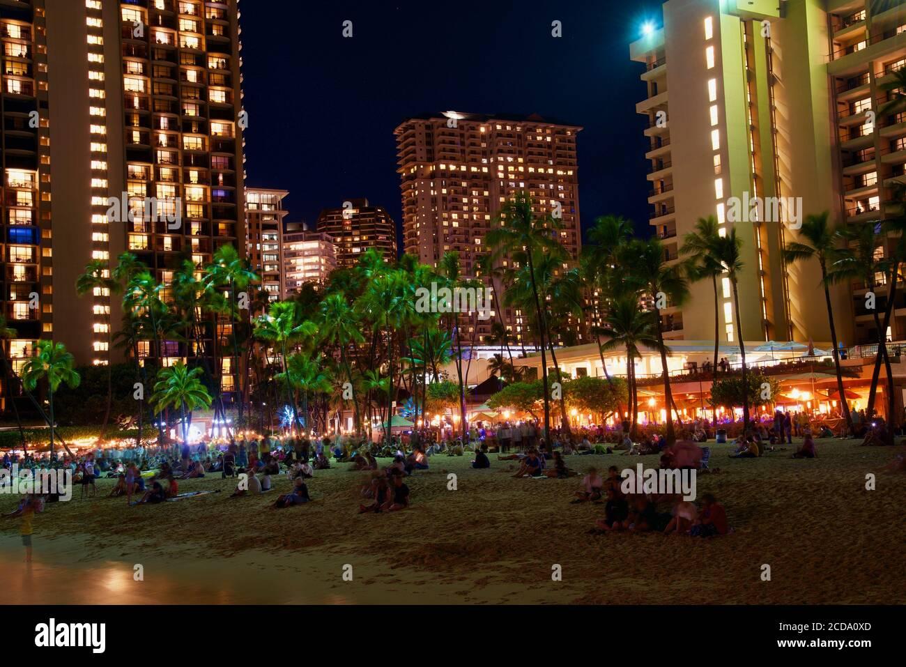 Crowds gathered to watch firework display over touristy beach, in front of hotel high rises, Waikiki Beach, Oahu Island, Honolulu, Hawaii, USA Stock Photo