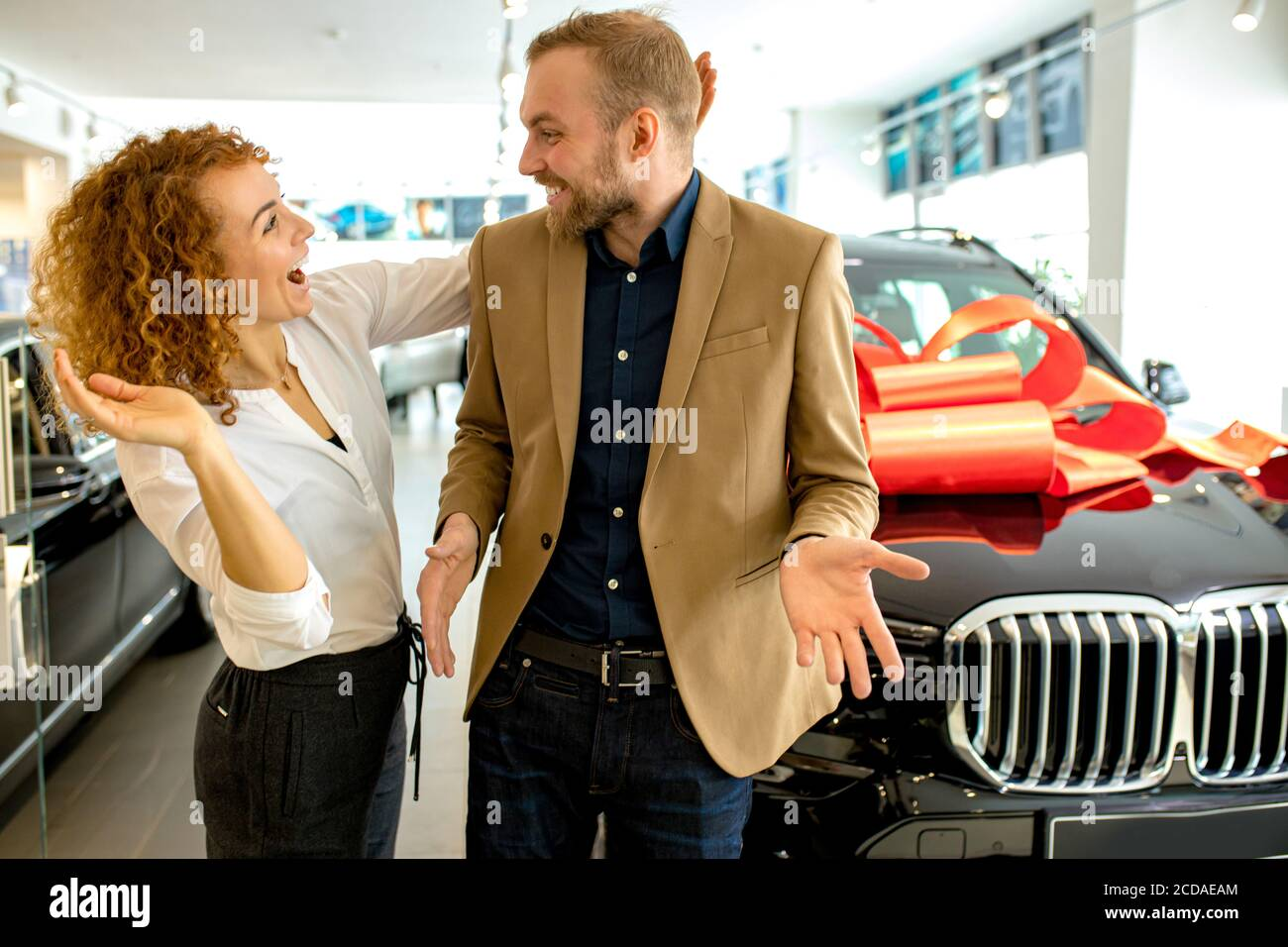 beautiful caucasian lady make surprise to husband in dealership. woman give new car wrapped in red bow to her husband, birthday gift. she openes man's Stock Photo