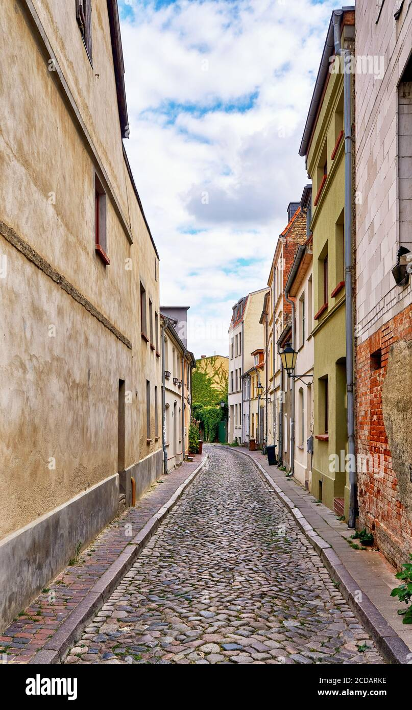 Narrow alley in the old town of Wismar. Old houses on a narrow street. Stock Photo