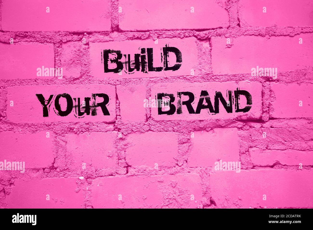 Build Your Brand. words on wall painted into pink. Marketing business concept Stock Photo