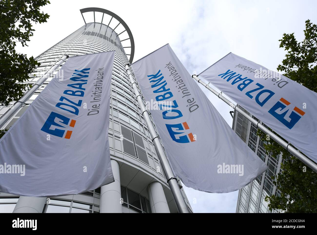 """25 August 2020, Hessen, Frankfurt/Main: Flags with the inscription """"DZ Bank - Die Initiativbank"""" are hanging in front of the office tower """"Westend 1"""", also known as the """"Kronenhochhaus"""", which belongs to the headquarters of DZ Bank. The Deutsche Zentral-Genossenschaftsbank (DZ Bank) presents figures for the first half of 2020 on 28.08.2020. Photo: Arne Dedert/dpa Stock Photo"""
