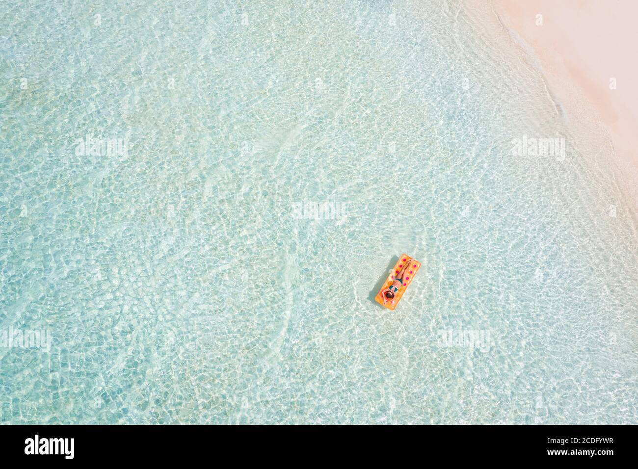 Top above high angle aerial drone view of fit slim wealthy rich healthy attractive girl experienced tourist floating lying on rubber mattress sea Stock Photo