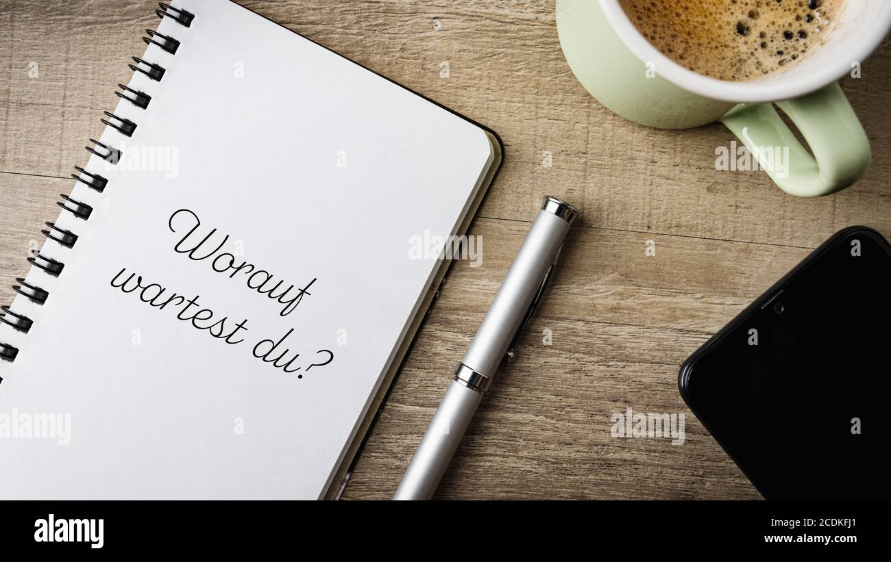 Worauf wartest du? German text. Translatiion: what are you waiting for? Flat lay. Work space with a note pad, ball pen, mobile and a cup of coffee. Stock Photo