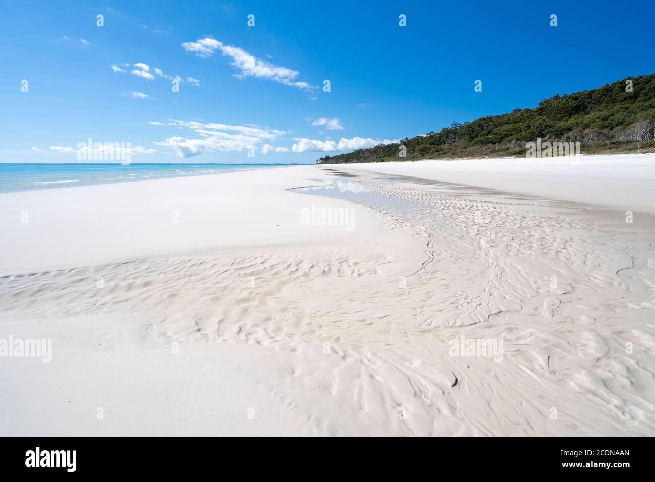 White sandy beach and clear water under blue sky, near Awinya Creek, western shore of Fraser Island, Hervey Bay Queensland Australia Stock Photo