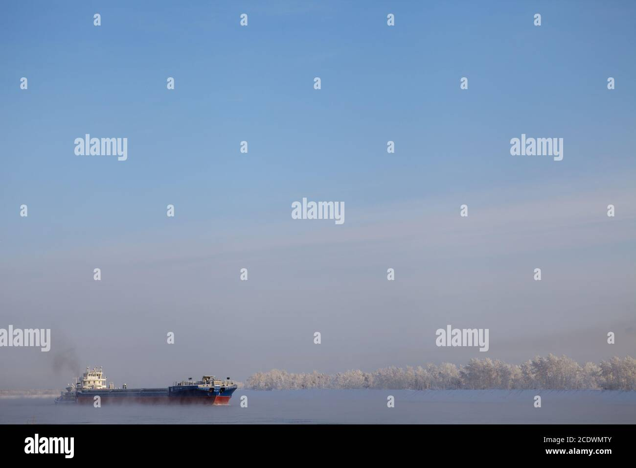Long barge going down river in cold winter. Stock Photo