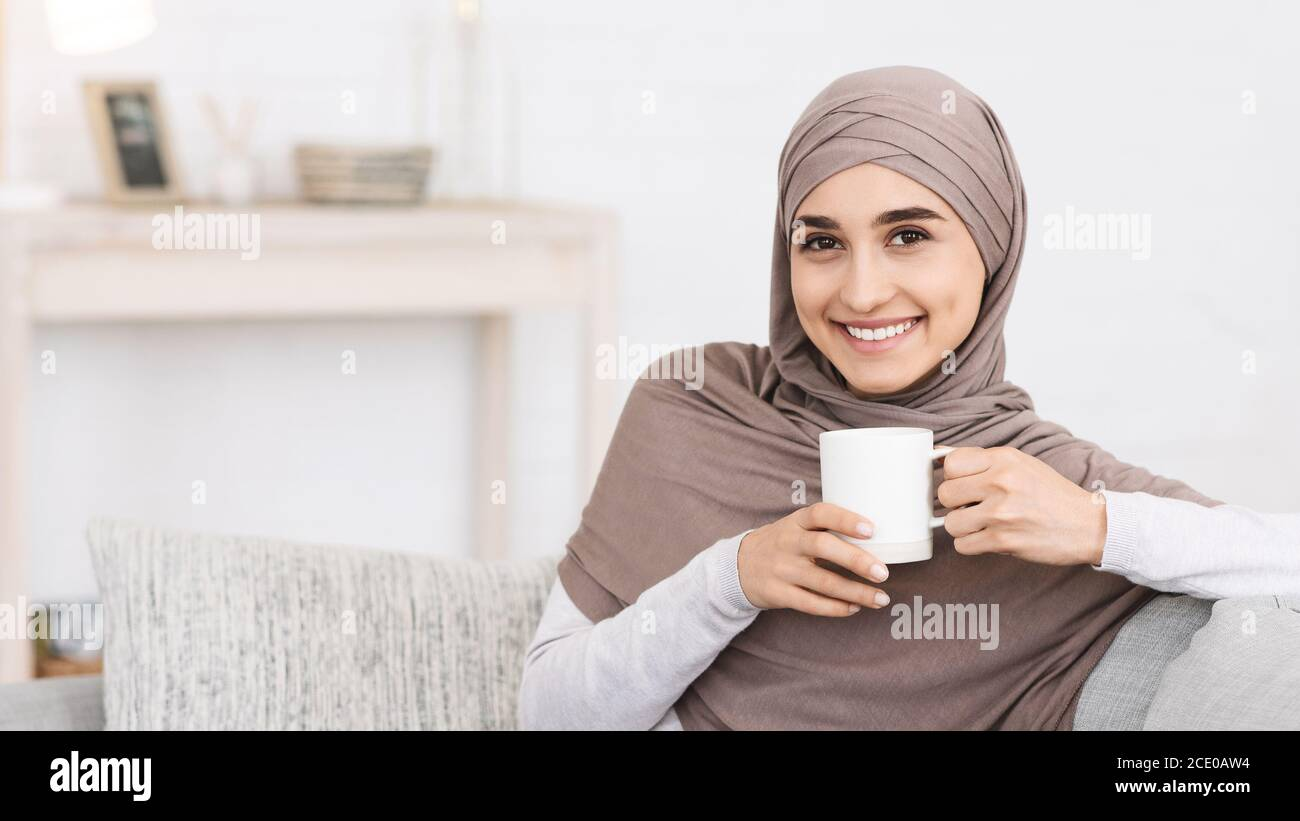 Domestic Relax. Smiling Arabic Girl In Hijab Relaxing On Couch With Coffee Stock Photo