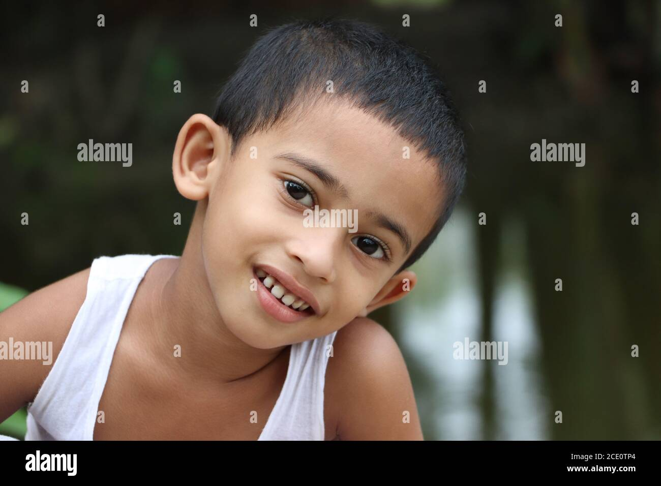 Cute little cheerful asian child looking at the camera, close up shot, eyes ear nose mouth Stock Photo