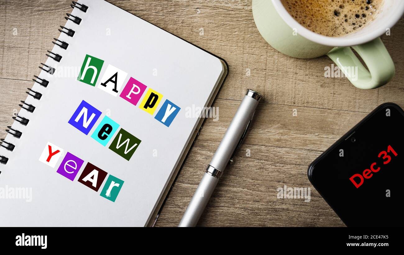 Dec 31. Happy New Year. Work space with a note pad, ball pen, mobile and a cup of coffee. Stock Photo