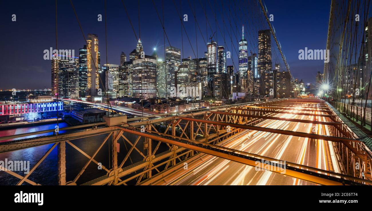 Panoramic view on Lower Manhattan skyscrapers at Dusk and Brooklyn Bridge with light trails. Evening in New York City, NY, USA Stock Photo