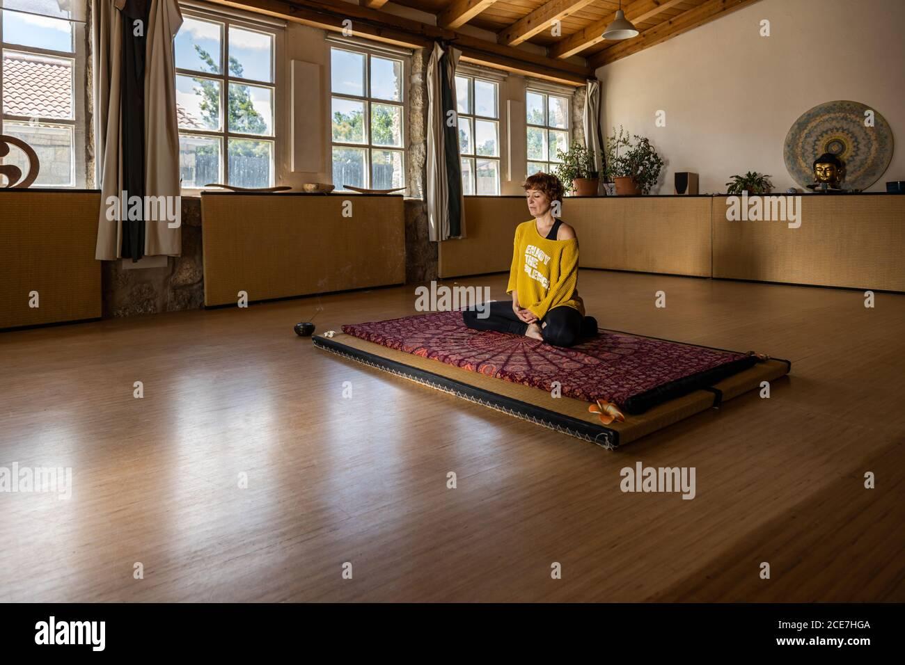 Calm female in sportswear sitting on mat in spacious studio and practicing yoga in Padmasana meditation Stock Photo