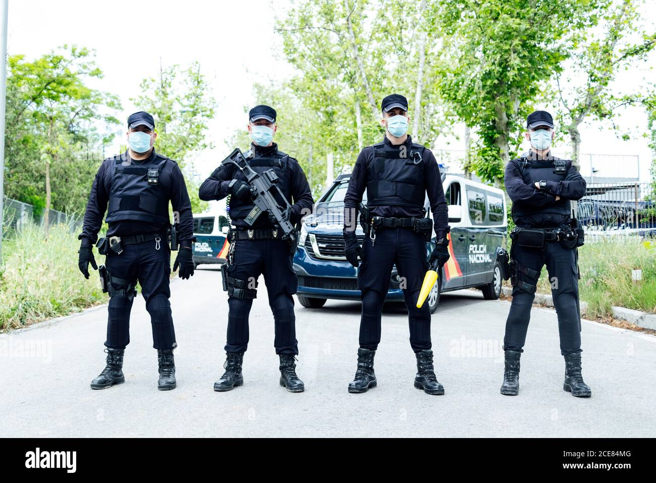 Full Body Squad Of Spanish Police Officers In Protective Gears With Guns Wearing Medical Masks During Patrolling Street Stock Photo Alamy