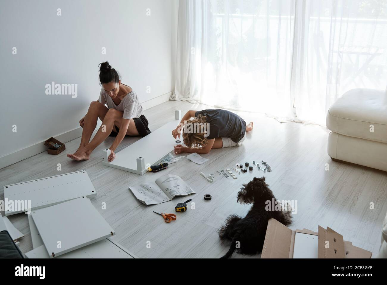 Preteen boy helping mother with fixing new wardrobe in light room with dog Stock Photo