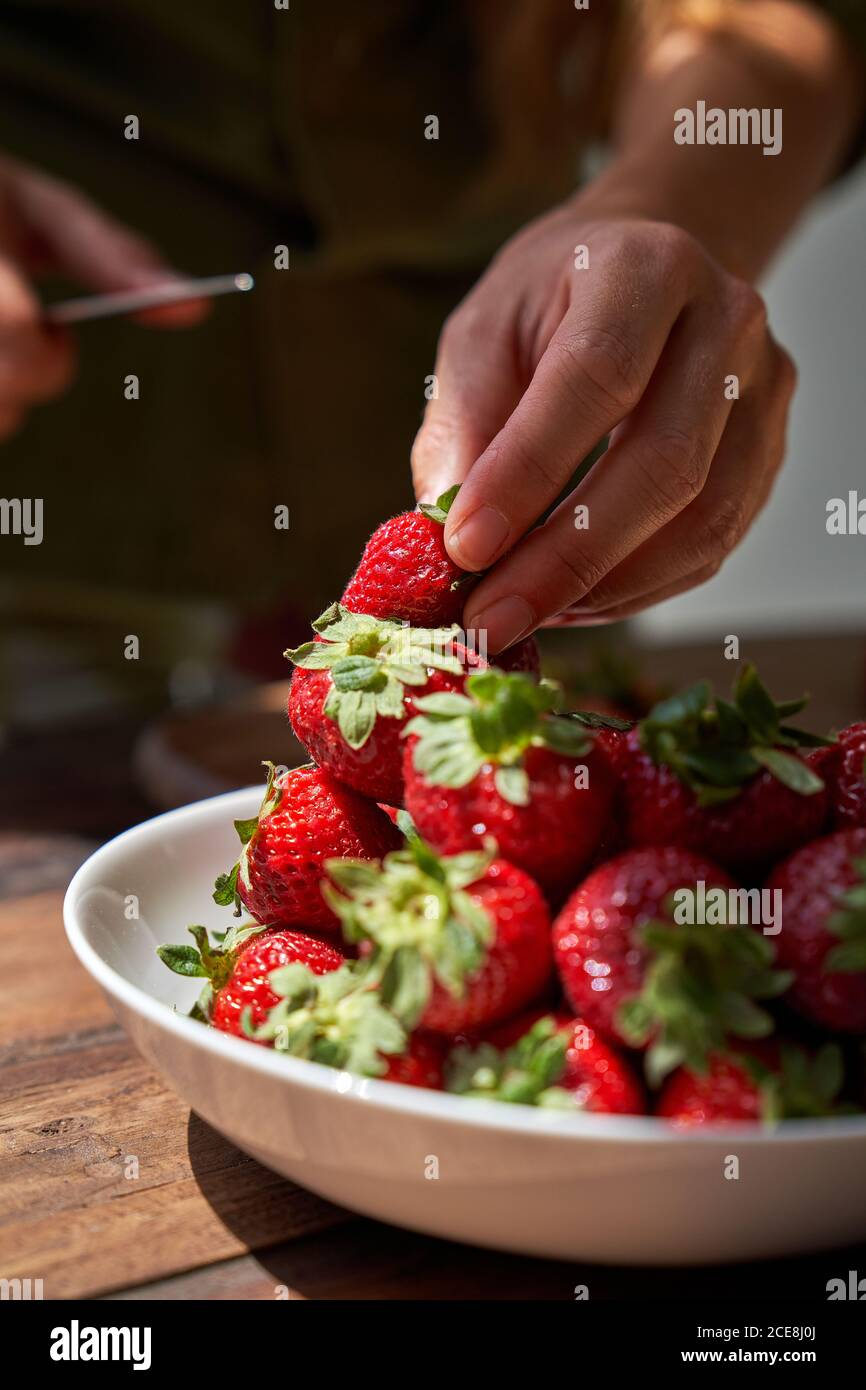 Female cook cutting fresh strawberry while preparing ingredients for homemade cake in kitchen Stock Photo