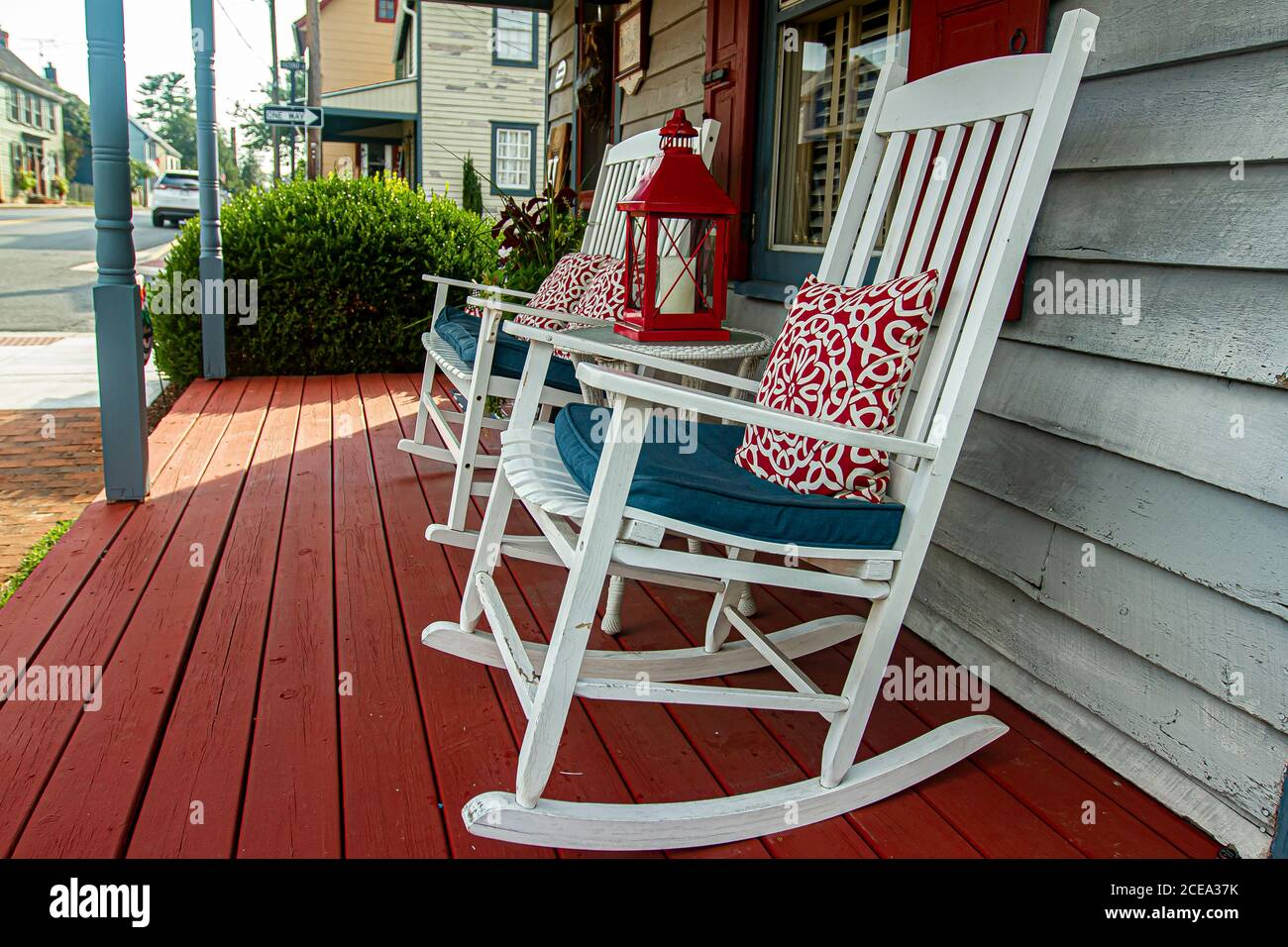 Chesapeake City, MD, USA 08/25/2020: Close up image of two white wooden traditional rocking chairs on a red painted porch of a 19th century American h Stock Photo