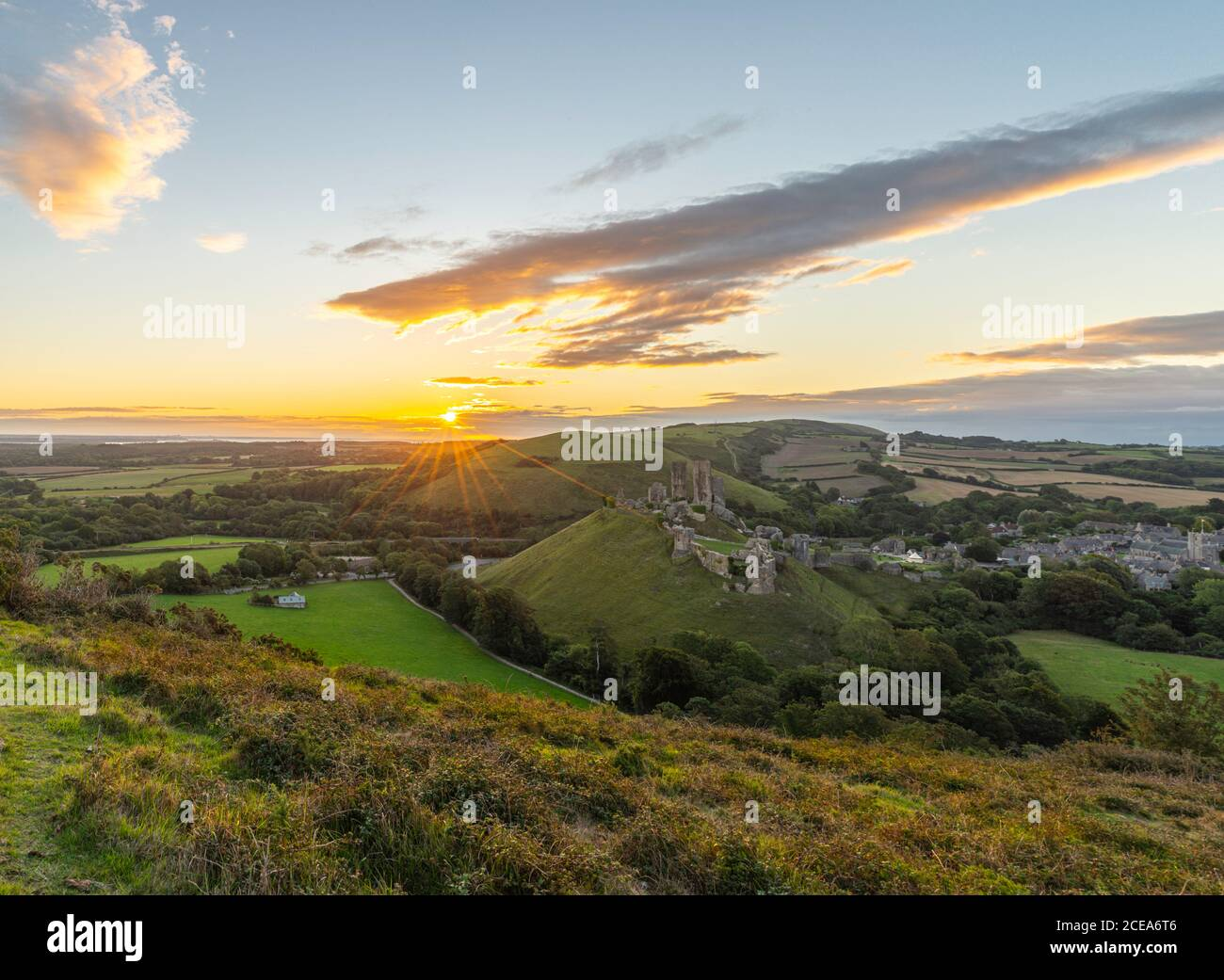 Sunrise with sunburst over the Dorset Countryside with Corfe castle and hills glowing from the morning sun. Stock Photo