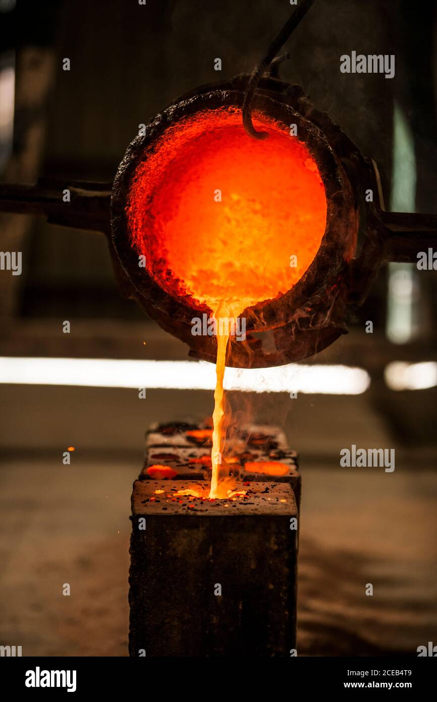 Hot molten metal pouring into casting mold in factory Stock Photo
